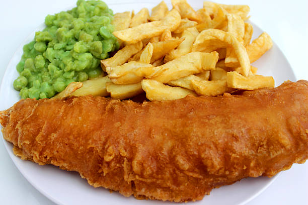 Battered fish and chips on white plate with mushy peas stock photo