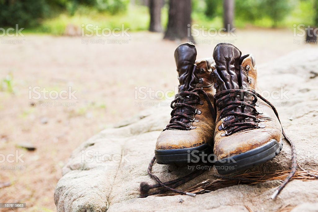 Battered hiking boots sit on a rock in forest clearing royalty-free stock photo