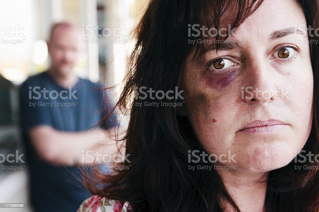 Battered woman gazes sadly at camera; bully lurks behind her stock photo