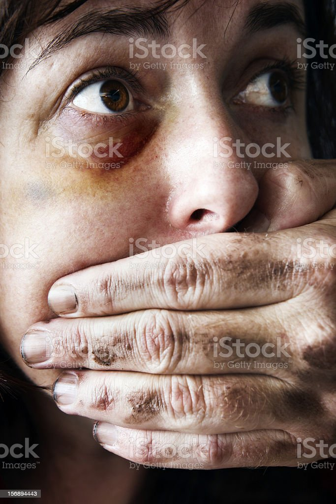 Battered woman is silenced by man's hand over her mouth stock photo