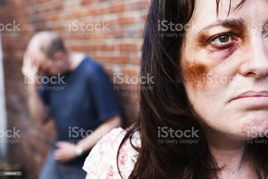Battered woman with remorseful partner in background stock photo