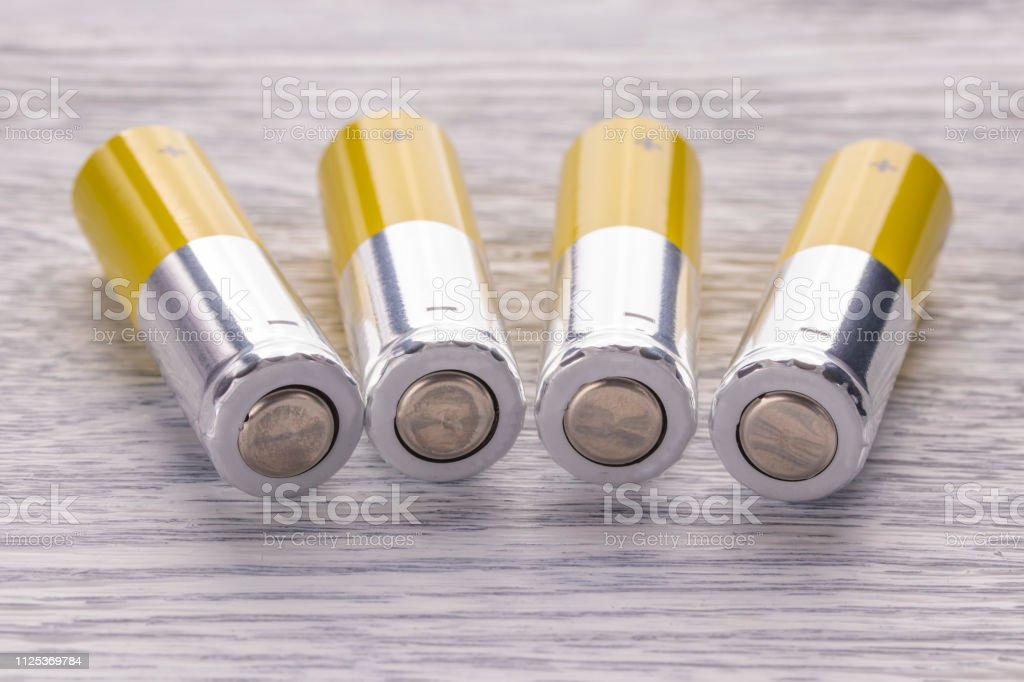 AA batteries on a white wooden table stock photo