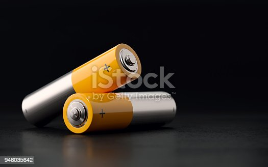 AA size yellow and silver colored  two batteries on black background with selective focus. Horizontal composition with copy space.
