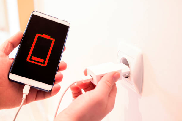 battery out of phone. phone charging from a wall outlet stock photo