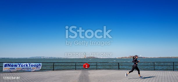 Manhattan, New York, USA - April 19,2020:  Young woman jogging for exercise, enjoys a warm spring day on the Battery park esplanade during the coronavirus pandemic