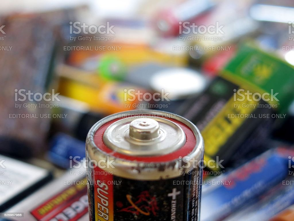 Battery size D in front of pile of dead batteries stock photo