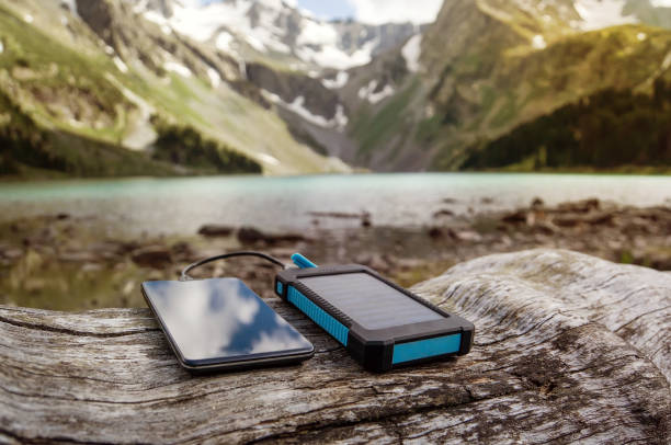 battery solar energy device on the background of beautiful mountain scenery. - power in nature stock photos and pictures