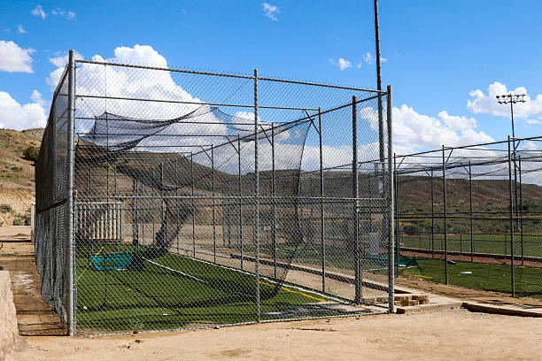 Batting cages with blue sky, puffy clouds and rolling hills