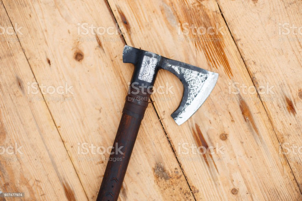Battle ax of the Vikings lies on a wooden shield stock photo