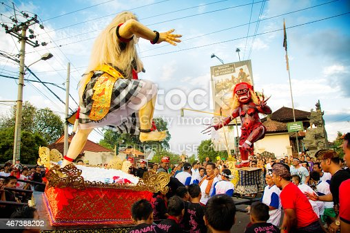 Lovina, Indonesia - March 20, 2015: Battle of the Ogoh-Ogohs during Nyepi Ngrupuk parade in Lovina, North Bali, Indonesia. The two handmade ogress statues, reprensenting all evil things in men are rushed forward by two groups of men and children, simulating a fight at the town square.