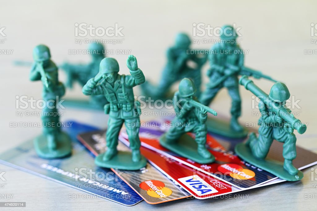 Batalla de presupuesto.   Juguete de soldados proteger las tarjetas de crédito, el gasto. - foto de stock