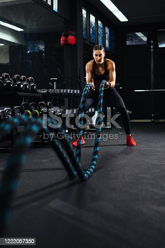 Young fit sportswoman working out with battle ropes at gym