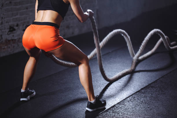 Battle ropes session. Attractive fit and toned sportswoman training in gym Battle ropes session. Attractive young fit and toned sportswoman training in gym desaturated stock pictures, royalty-free photos & images