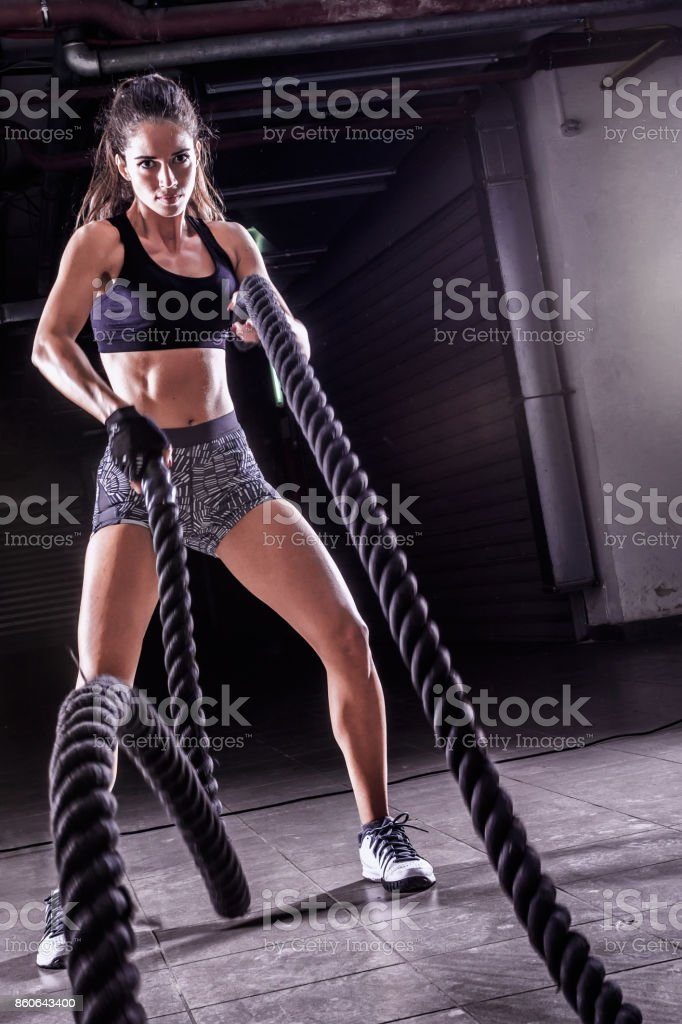 Battle ropes session. Attractive young fit sportswoman working out in training gym stock photo