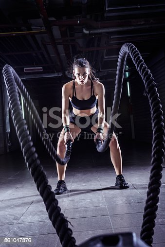 istock Battle ropes session. Attractive young fit sportswoman working out in training gym 861047876