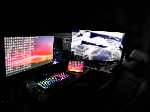 schlachtstation gaming-rigg mit mehreren monitoren für gamer-bergleute designer renderers in einem dunklen raum mit rgb-leuchten auf - kostenlose onlinespiele stock-fotos und bilder