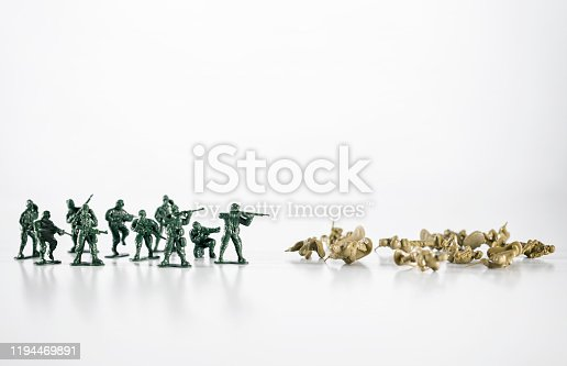 Battle, two small armies with toy soldiers, one is winning, another is loosing. Selective focus, white background.