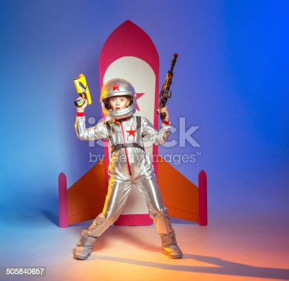 Funny girl astronaut with space handguns in her hands is playing in space combat against the backdrop of toy rocket
