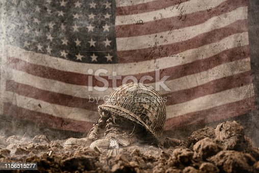 A muddy army helmet sitting atop a pair of empty army boots with a pair of dog tags as a memorial to a fallen soldier in battle with a 48 star US flag hanging in the background. This could be from World War II or the Korean war.
