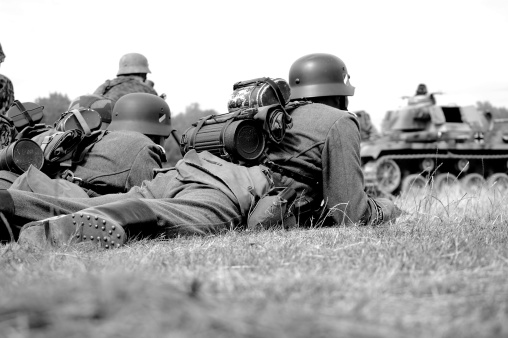 WW2 German combat troops lay down ready to attack an enemy position.Picture taken during a major battle re-enactment at the War and Peace show.Has been aged to give the feel of a vintage shot