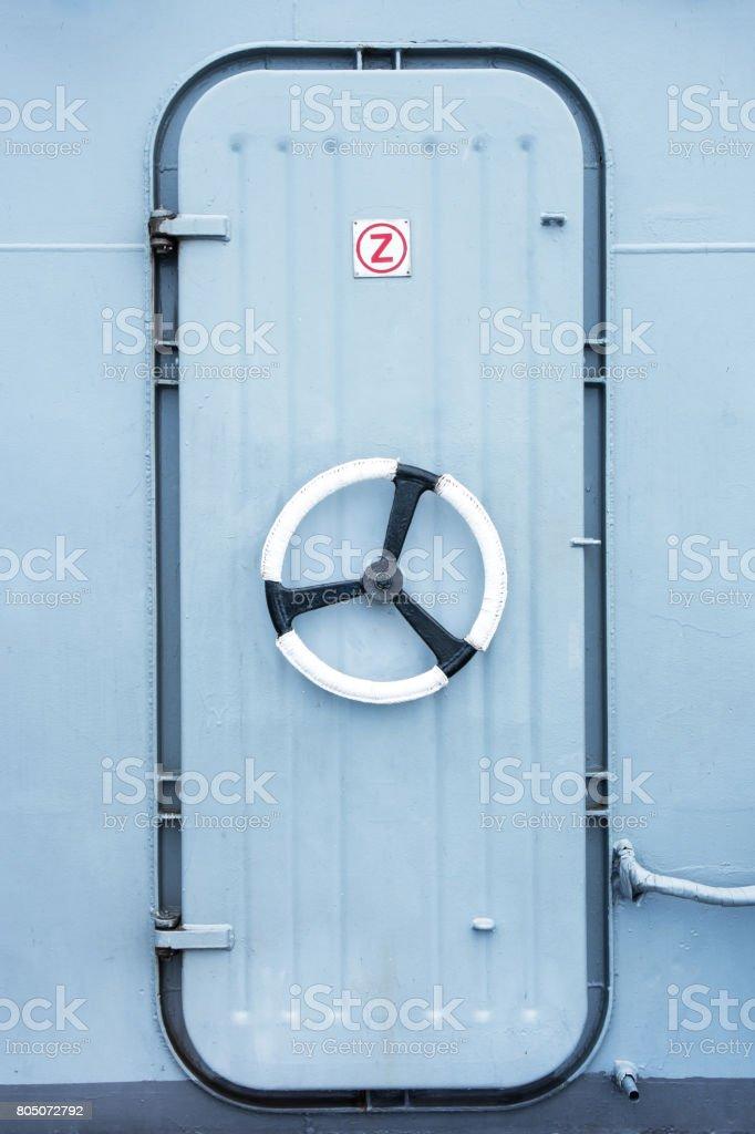 Battleship iron door with steering wheel lock background stock photo