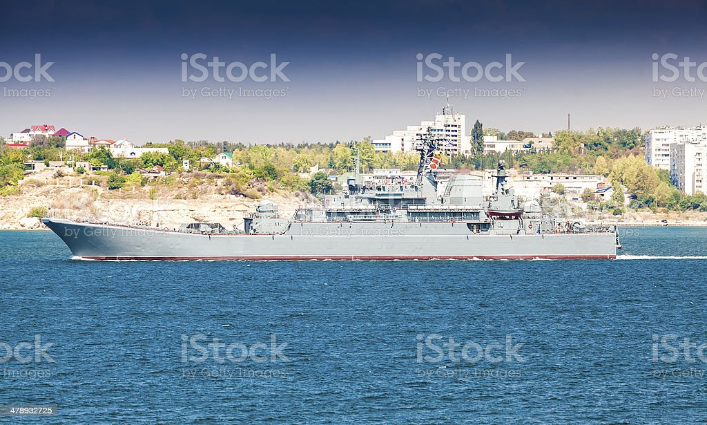Battleship sailing from port stock photo