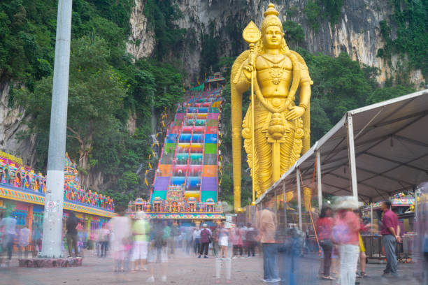 Batu Caves with construction Batu Caves near Kuala Lumpur, Malaysia. The photo is a long exposure with blurry people. Under the Murugan Statue is a construction tent. batu caves stock pictures, royalty-free photos & images