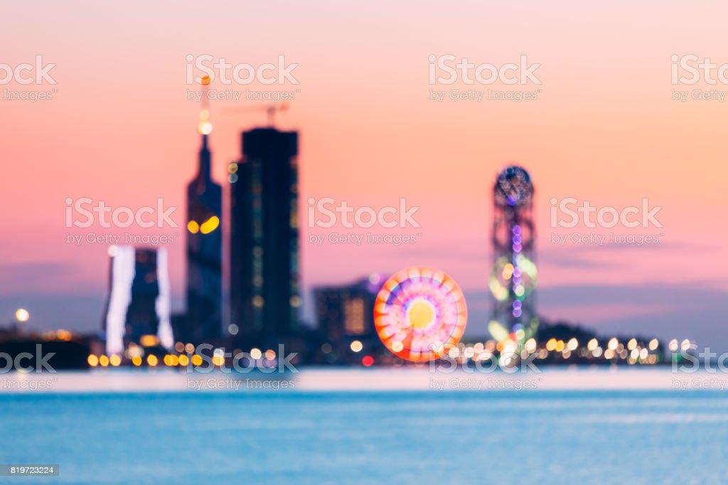 Batumi, Adjara Georgia. Abstract Blurred Bokeh Boke Background Of Illuminated Ferris Wheel, Skyscrapers And Modern Urban Architecture In Embankment Of Georgian Resort Town Of Batumi stock photo