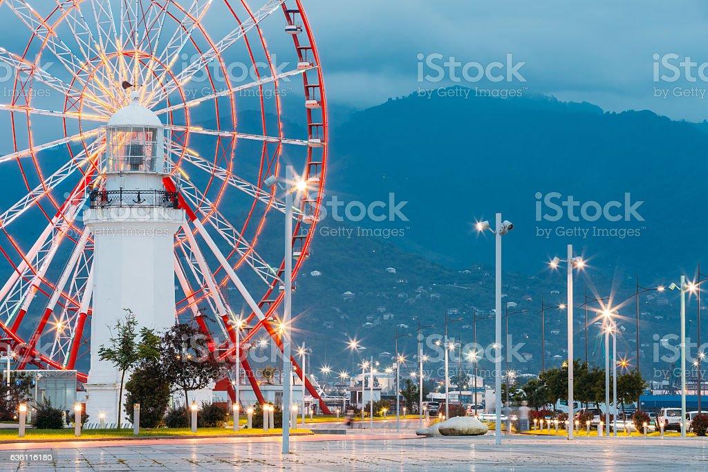 Batumi Georgia. Close Ferris Wheel Behind Old White Lighthouse stock photo