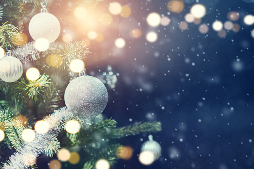 istock Bauble hanging from a decorated Christmas tree with bokeh and snow, copy space. Xmas holiday background. 1172243894