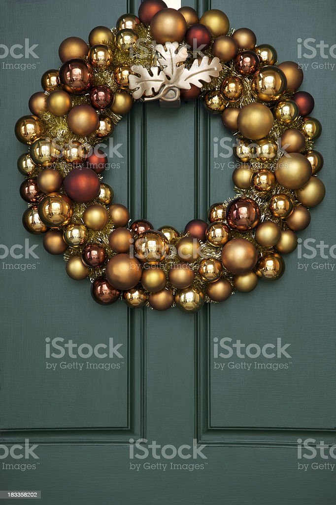 Baubles in Holiday Wreath on Green Paneled Door royalty-free stock photo
