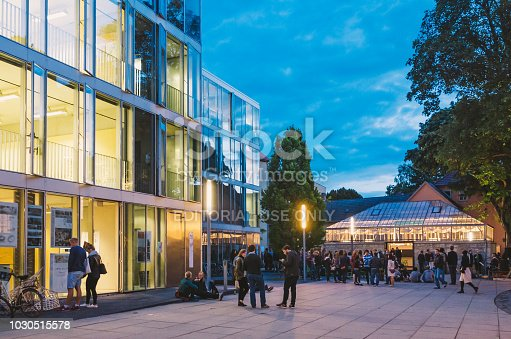 Weimar, Germany - October 03, 2015: Students sitting and standing at the Campus of Bauhaus University at Dusk.