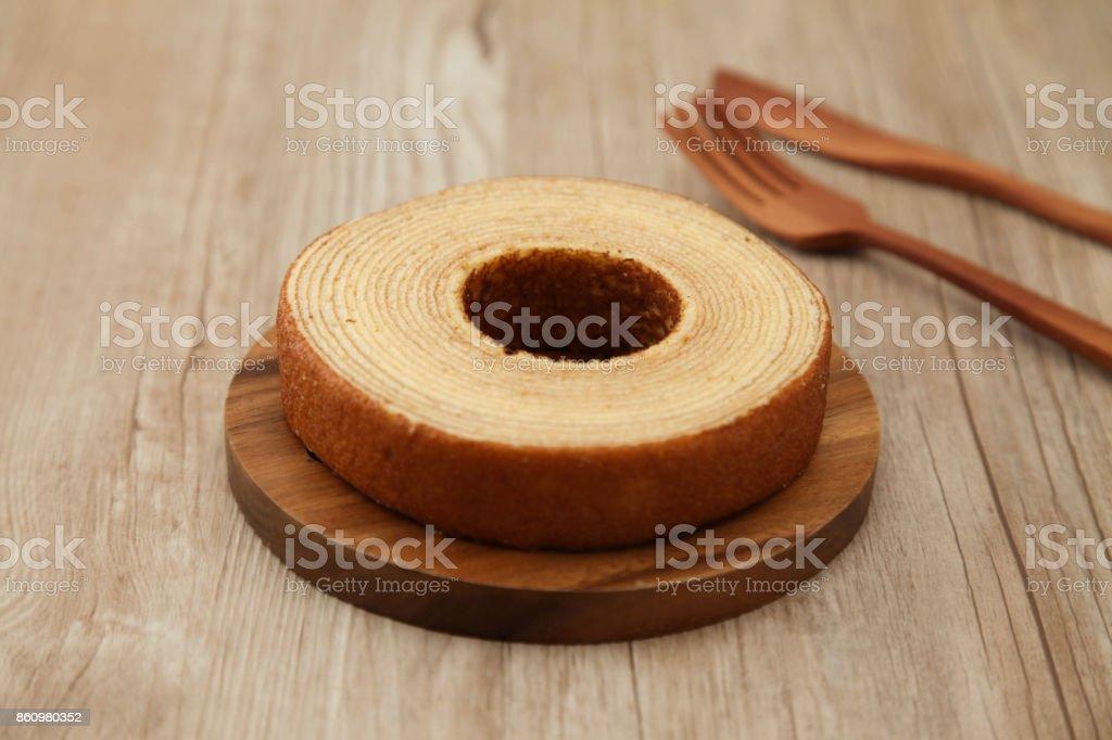 Baumkuchen deutsche Krapfen Kuchen auf Holzplatte Gabel Messer auf Tisch – Foto