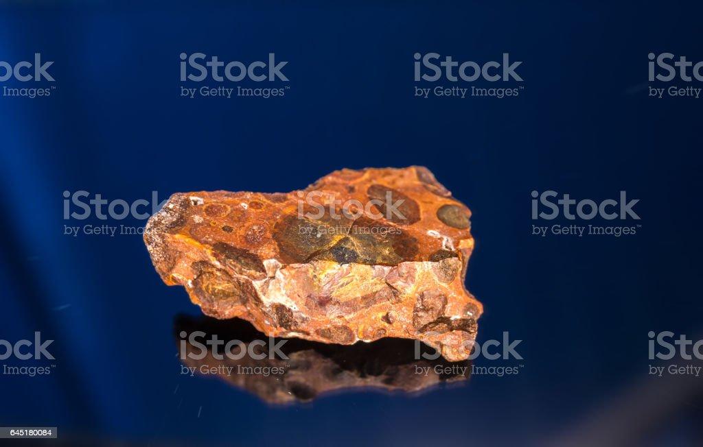 Bauxite mineral under sun light on dark background - Photo