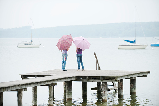 Bavaria, Ammersee two Women standing on jetty holding umbrellas
