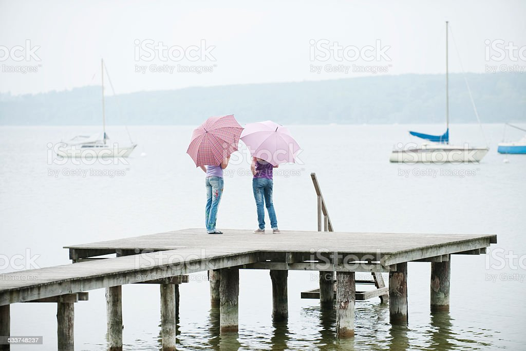 Bavaria, Ammersee two Women standing on jetty holding umbrellas stock photo