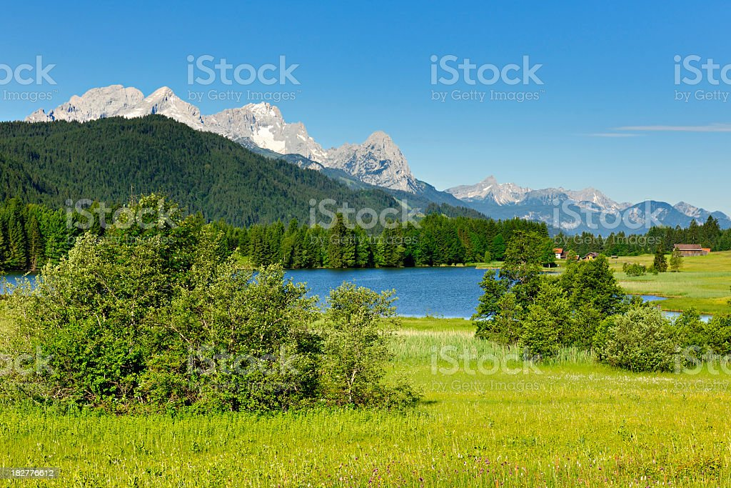 Bavaria Landscape with Barns and Lake against Mount Zugspitz royalty-free stock photo