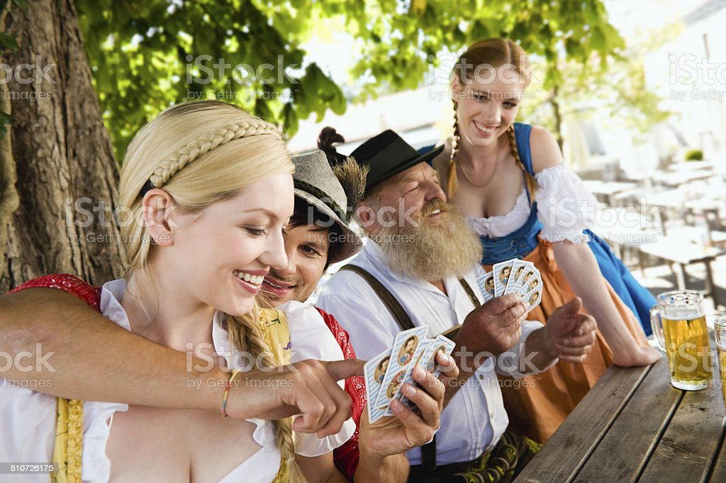 Bavaria, people in traditional costume playing cards in beer garden stock photo