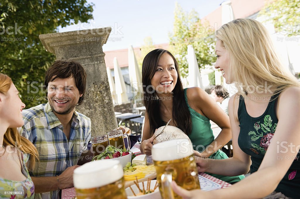 Bavaria, young adults sitting in beer garden drinking beer stock photo