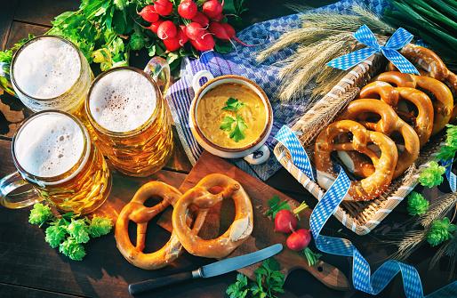 Bavarian beer with soft pretzels, obatzter and radish on rustic wooden table. Oktoberfest menu