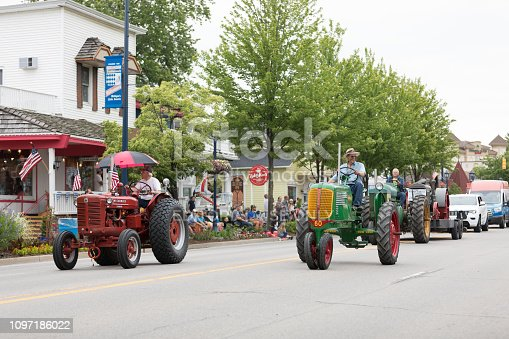 Frankenmuth, Michigan, USA - June 10, 2018: The Bavarian Festival Parade, A group of vintage tractors going down the road during the parade
