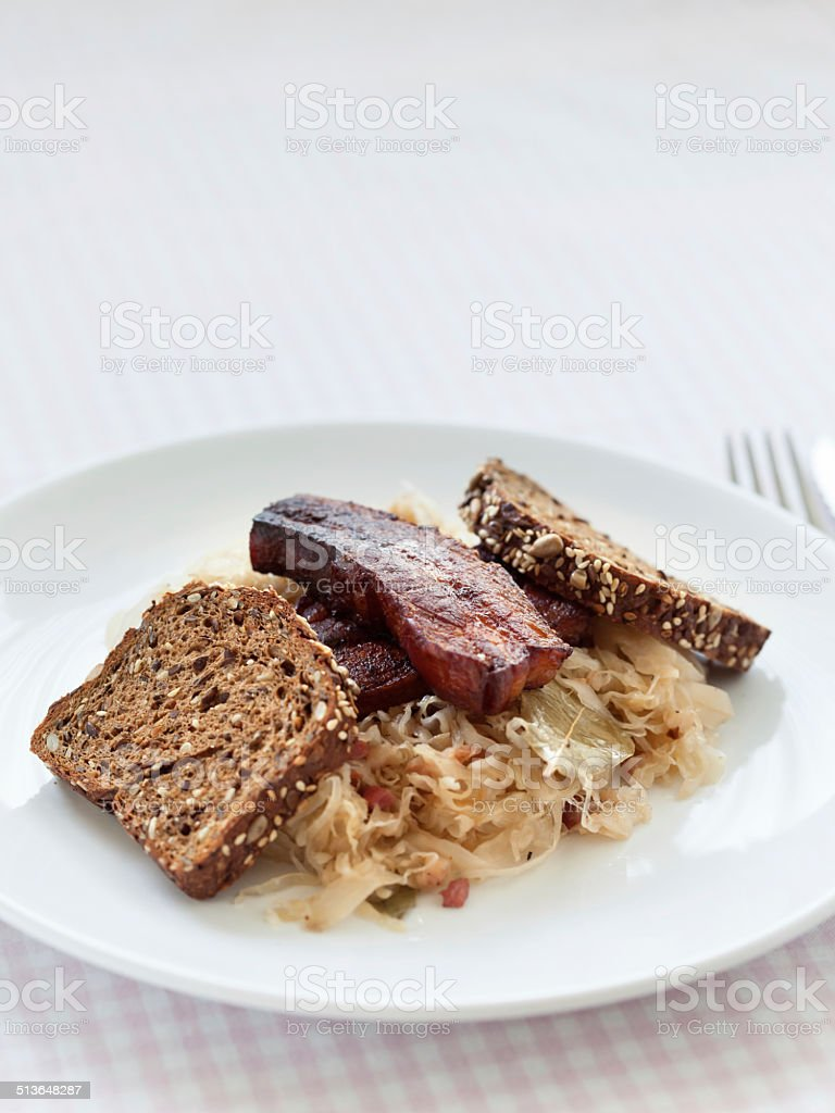 Bavarian fried bacon served with sauerkraut in a pan stock photo