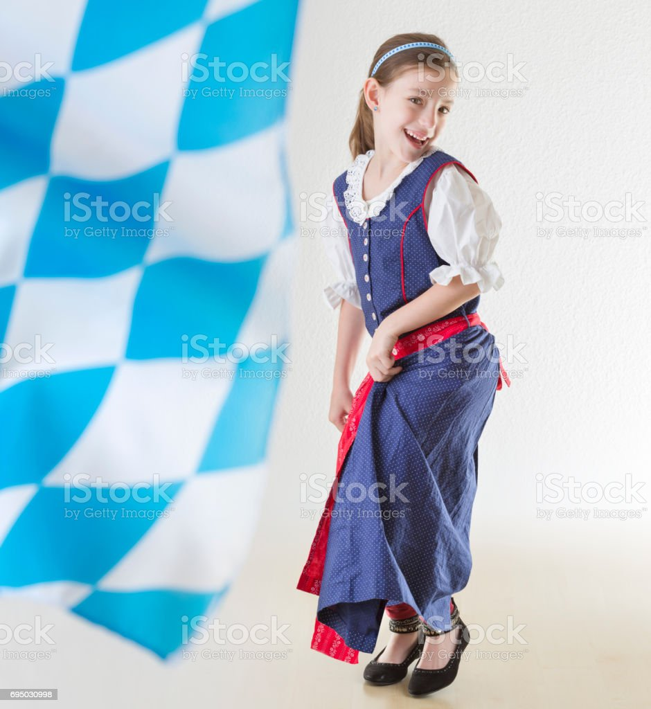 b2d5fd9bd6d7 Bavarian little girl in traditional dress Dirndl and bavarian flag dancing  - Stock image .