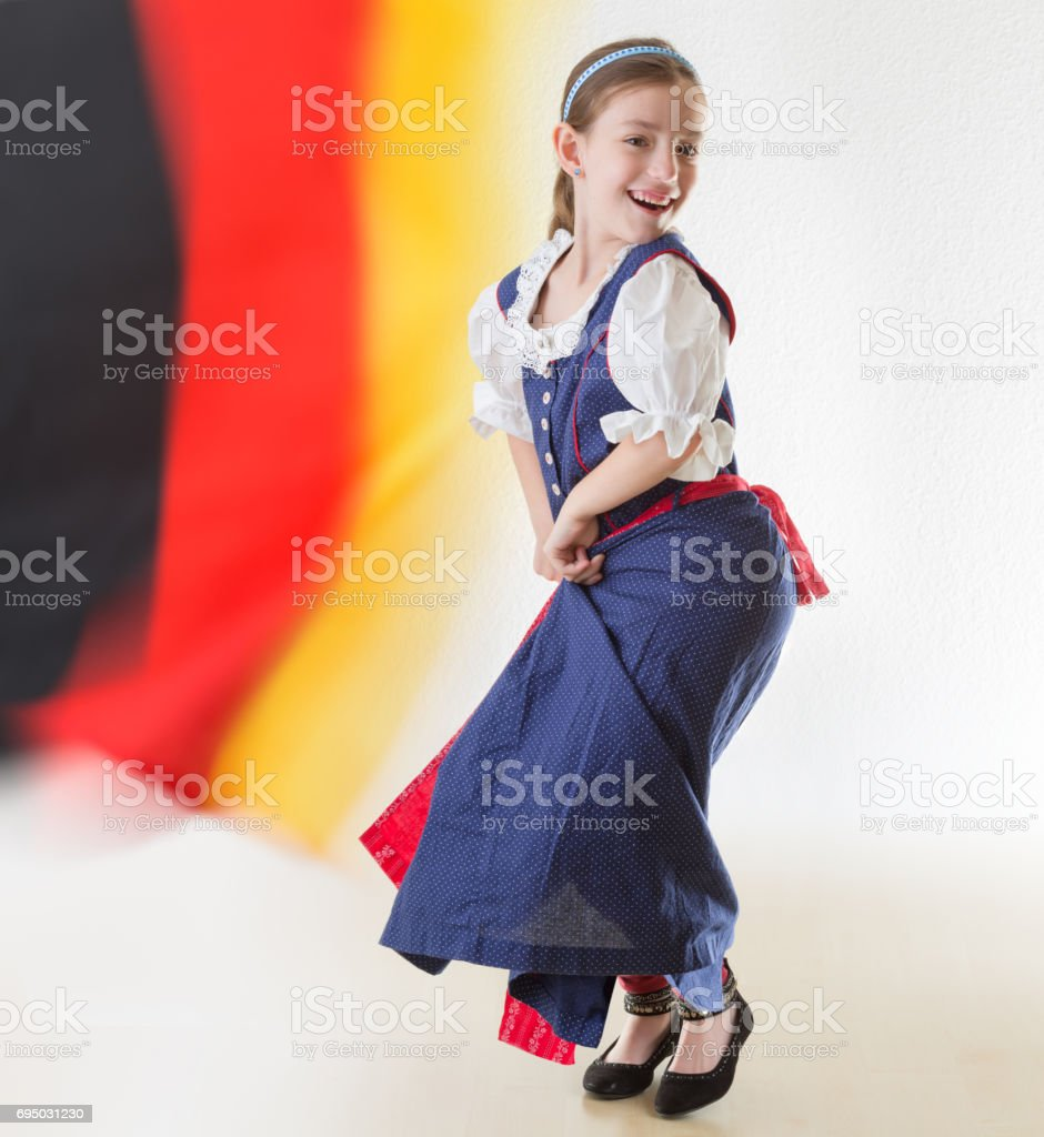 169796aba414 Bavarian little girl in traditional dress Dirndl dancing with german flag -  Stock image .