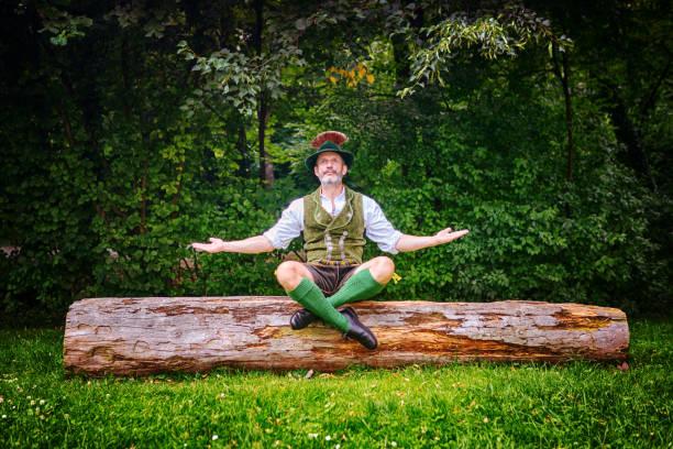 bayerischen mann auf baumstumpf sitzen und meditieren - bayerische tracht stock-fotos und bilder