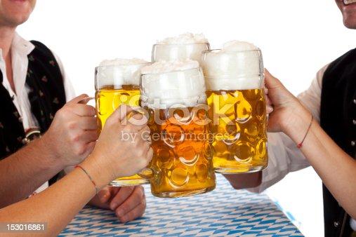 istock Bavarian men and women toast with Oktoberfest beer stein 153016861