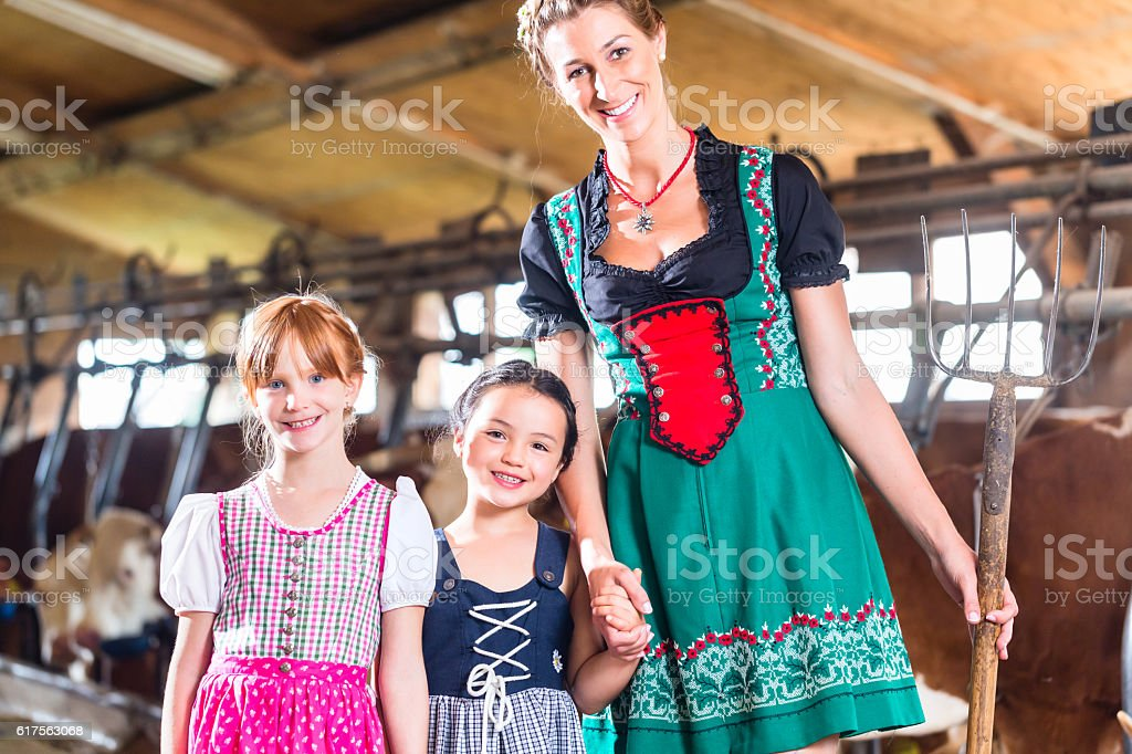 Bavarian mother showing children cows in cow farm stock photo