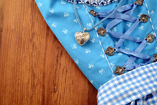 Bavarian Oktoberfest dirndle on wooden table with necklace heart