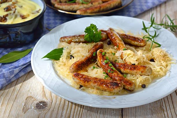bayerischen würstchen - bratwurst mit sauerkraut stock-fotos und bilder