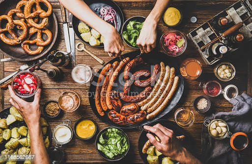 Flat-lay of Octoberfest dinner table concept with grilled sausages, pretzel pastry, potatoes, cucumber salad, sauces, beers and peoples hands with holding snacks over dark wooden background, top view